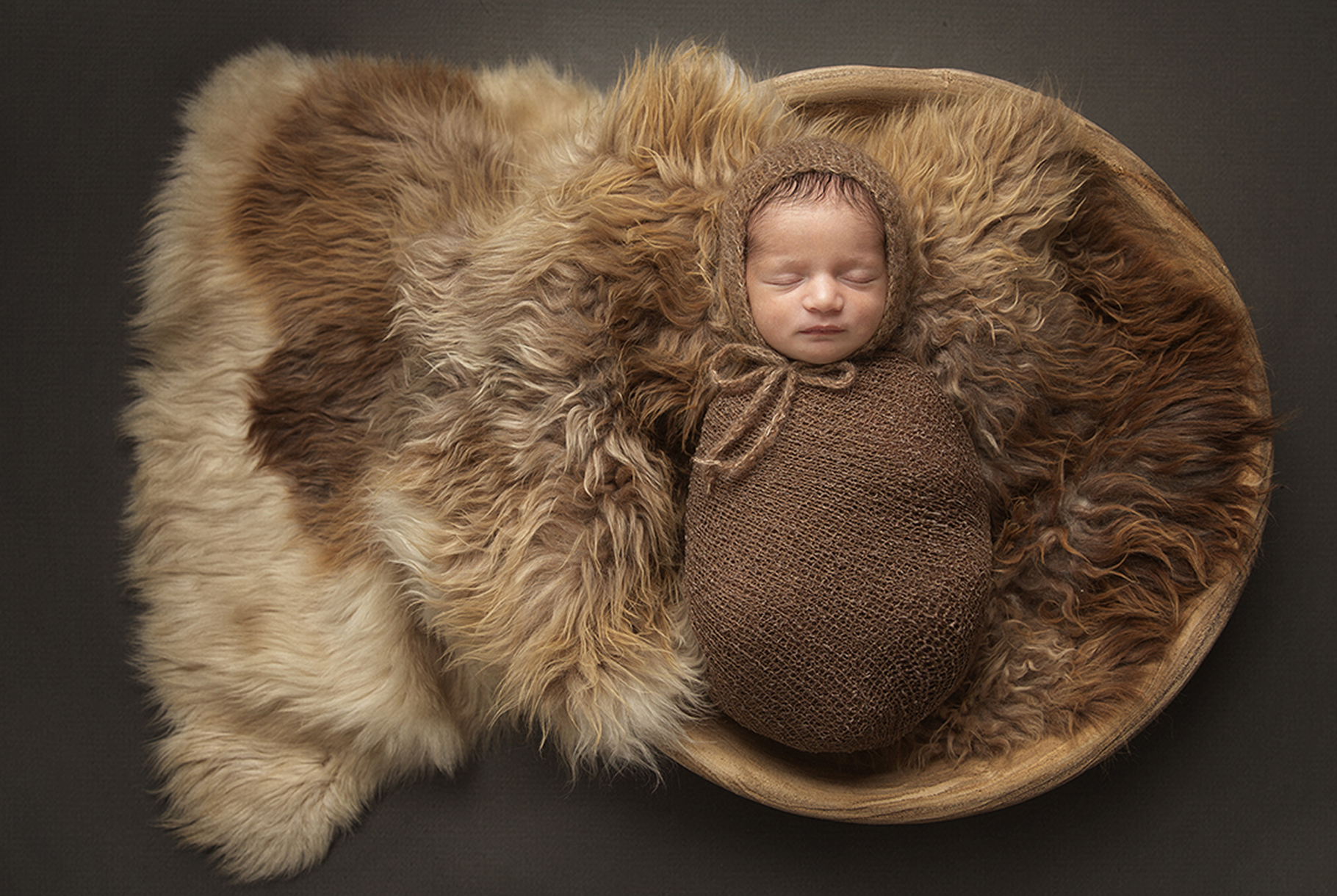 baby wrapped in bowl on brown rug by newborn photographer Dumfries