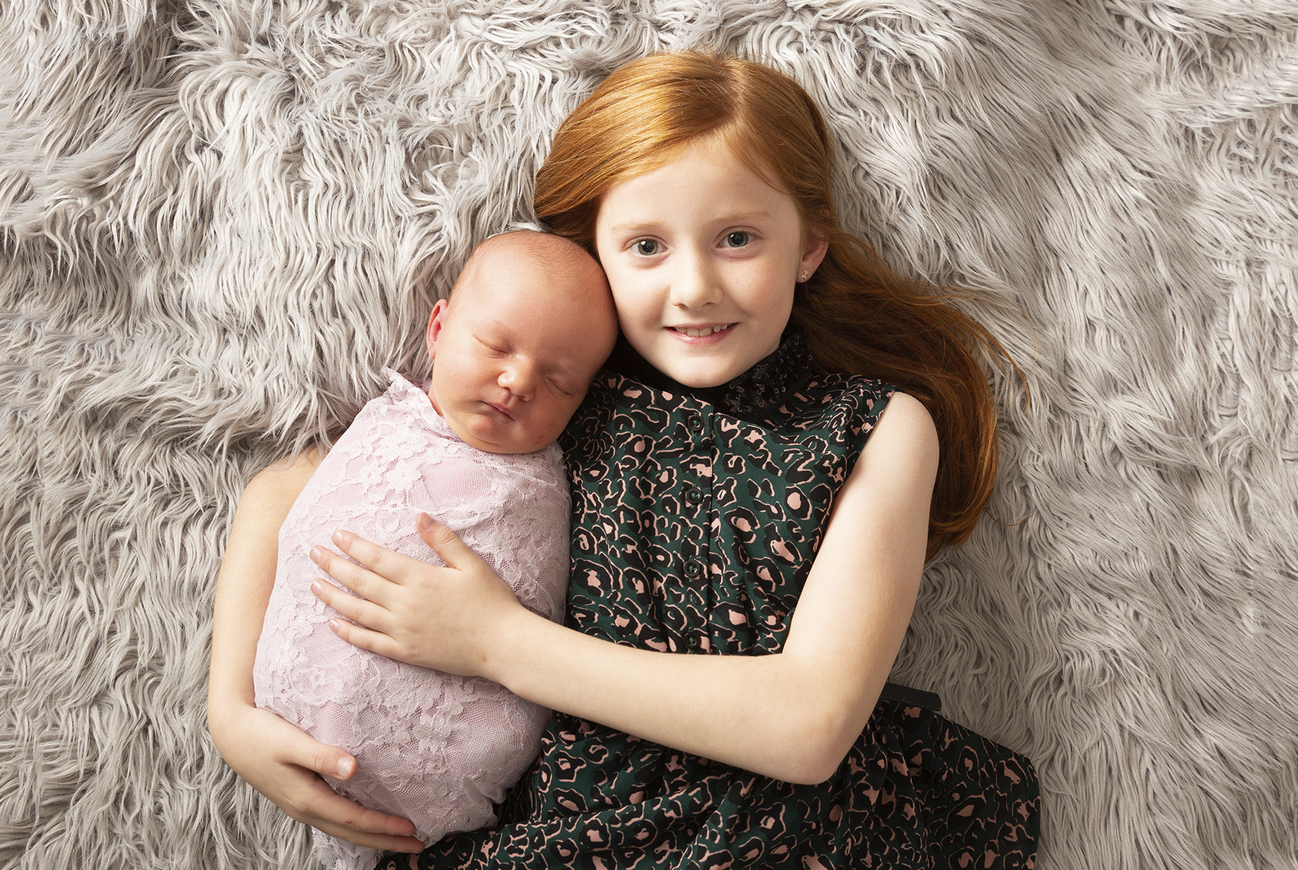 sisters lying cuddling on rug by newborn photographer Dumfries