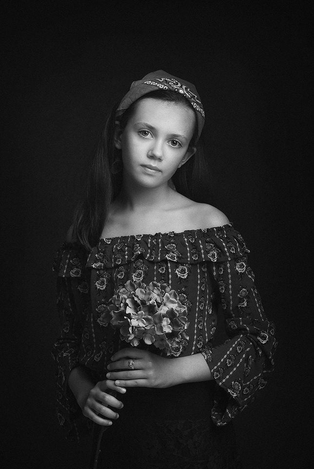 girl holding flowers wearing a headband by children's photographer Dumfries