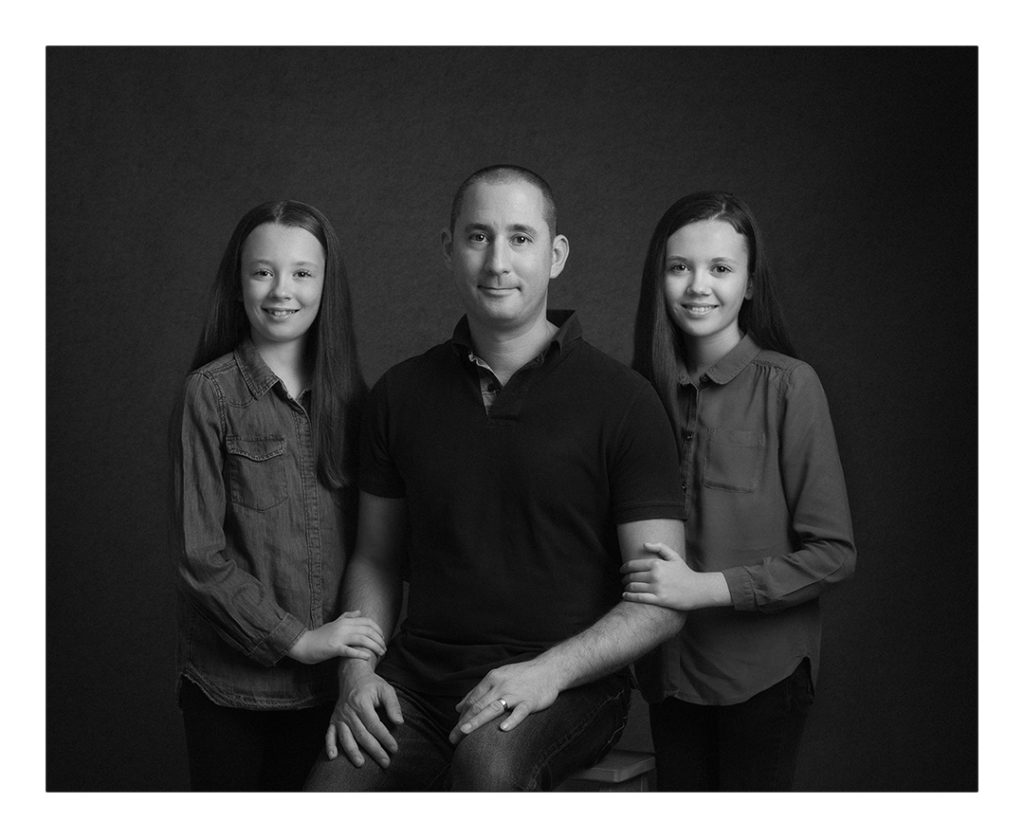 photography of a father and his 2 daughters