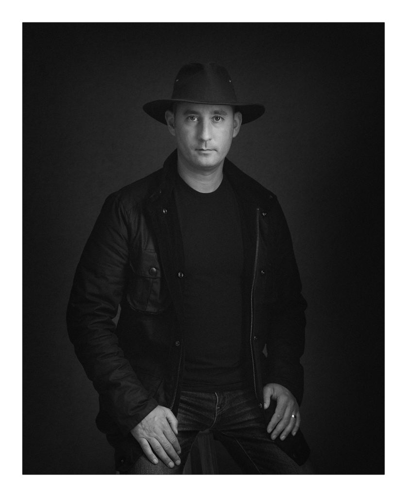 photograph of a man in a hat wearing a barbour jacket