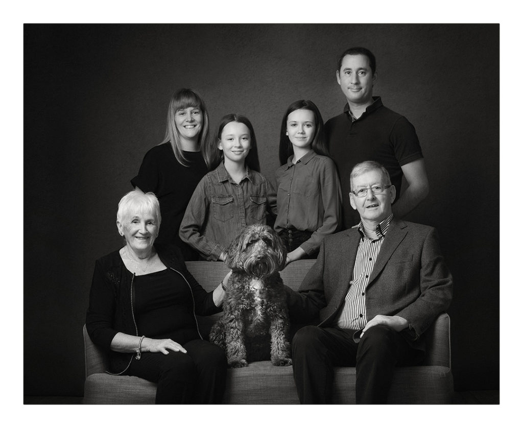 family portrait including grandparents and a dog