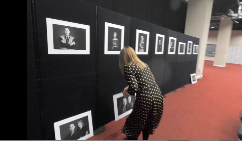 woman positioning photographs as part of a display