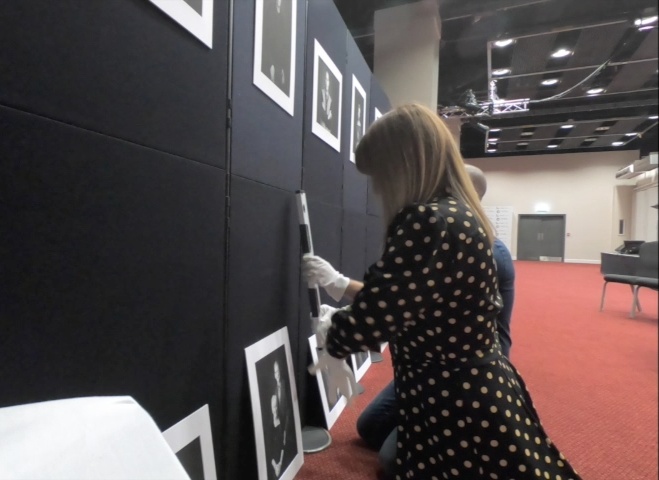 woman measuring the position of a photography display