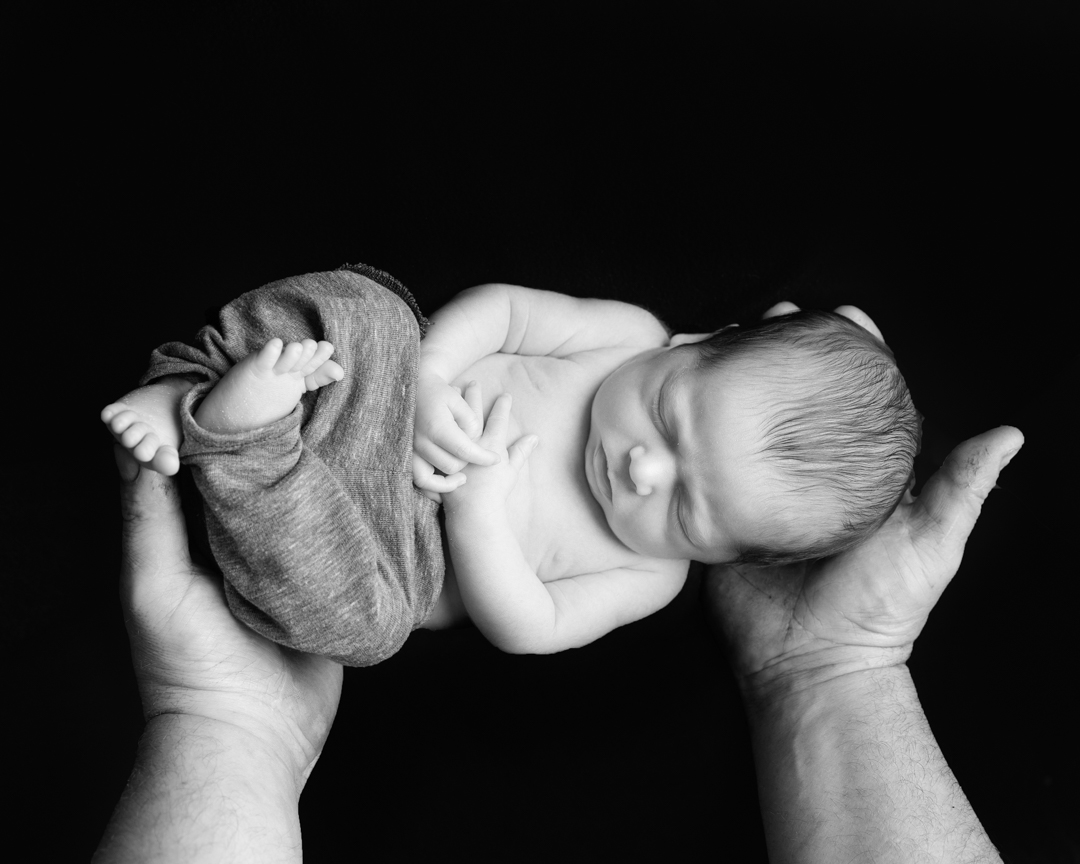 black and white photograph of baby in dads hands