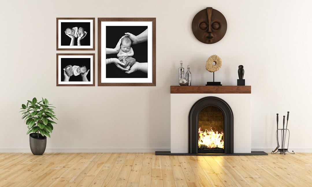 image of three newborn portraits framed and displayed on a wall of a living room beside a fireplace