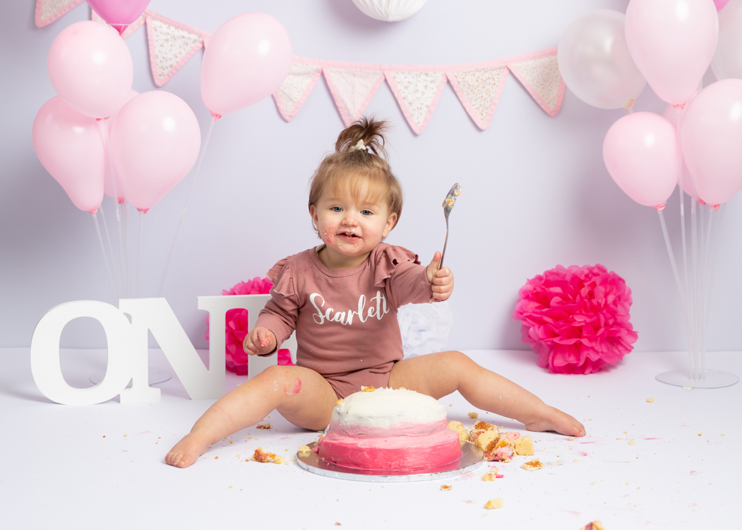 little girl dressed in pink smashing up a cake