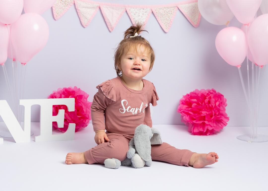 little girl sitting on floor celebrating her first birthday