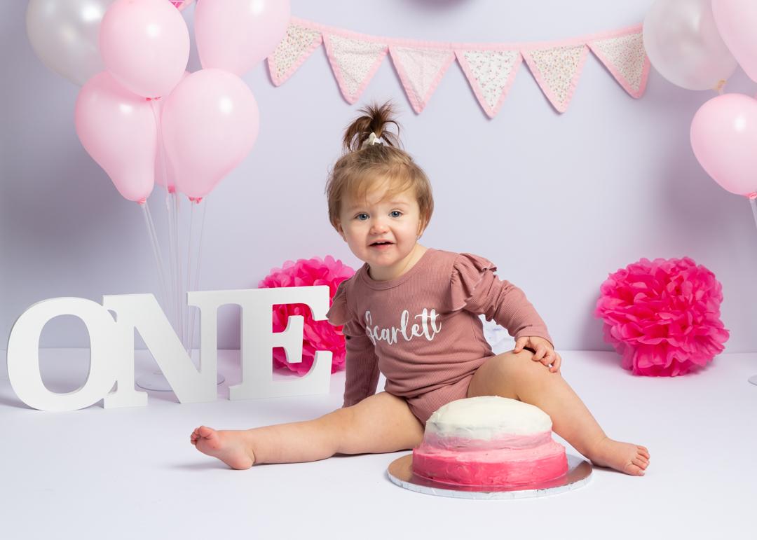 little girl sitting on floor in front of cake