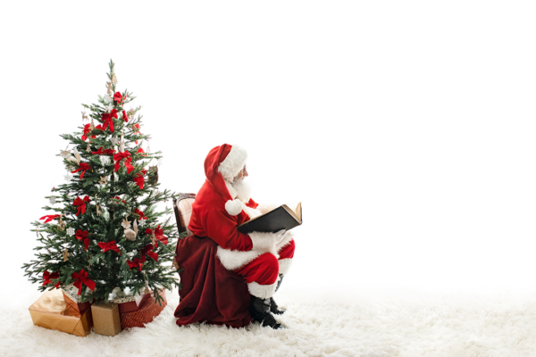 Father Christmas sat reading a book beside a Christmas tree